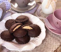 Biscotti al cioccolato ripieni di crema bianca alle nocciole